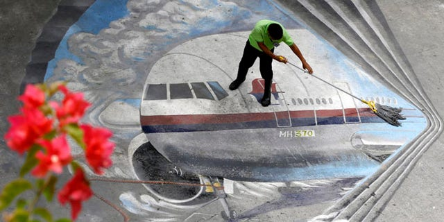 """April 8, 2014: A school utility worker mops a mural depicting the missing Malaysia Airlines Flight 370 at the Benigno """"Ninoy"""" Aquino High School campus at Makati city east of Manila, Philippines."""