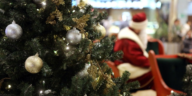 Santa Claus in Shopping Center on defocused lights background