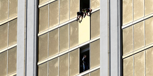 Workers board up a broken window at the Mandalay Bay hotel were Stephen Paddock fired from.