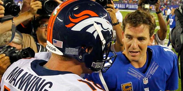 Denver Broncos quarterback Peyton Manning (L) talks with his brother, New York Giants quarterback Eli Manning after the Broncos defeated the Giants in their NFL football game in East Rutherford, New Jersey, September 15, 2013. REUTERS/Gary Hershorn (UNITED STATES - Tags: SPORT FOOTBALL) - RTX13MSZ