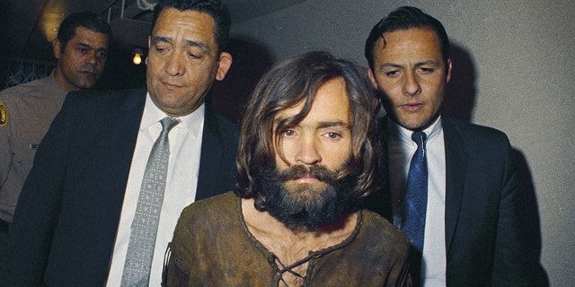 In this 1969 file photo, Charles Manson is escorted to his arraignment on conspiracy-murder charges.