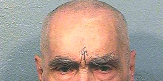 Charles Manson in prison with a swastika carved into his forehead.