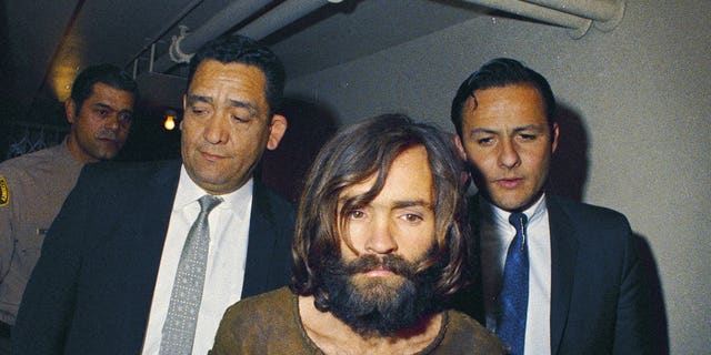 FILE - In this 1969 file photo, Charles Manson is escorted to his arraignment on conspiracy-murder charges in connection with the Sharon Tate murder case. Authorities say Manson, cult leader and mastermind behind 1969 deaths of actress Sharon Tate and several others, died on Sunday, Nov. 19, 2017. He was 83. (AP Photo, File)