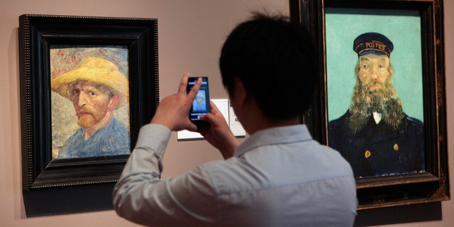 """A visitor at the Detroit Institute of Arts museum uses his cell phone to take a picture of the """"Self Portrait,"""" painting by Vincent van Gogh. (REUTERS/Rebecca Cook)"""
