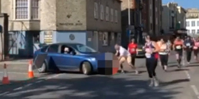 """The moment when a woman tried to drive into the route of the Plymouth half marathon - while the race was underway. See SWNS story SWRACE; One of Devon's most successful athletes has slammed a woman who drove her car on the route of race in Plymouth this morning. Hundreds of participants were left aghast as the woman knocked over road closure cones and attempted to cross the path of runners taking part in the Britain's Ocean City Half Marathon today. The incident, which was captured on film by eyewitness Rob Bricknell, left many people in shock - one of whom was Plymouth's GB Sprint Hurdler David King. He took to Twitter to express his disbelief. He described it as """"disgusting behaviour"""" and said """"you need to watch the video to believe it""""."""