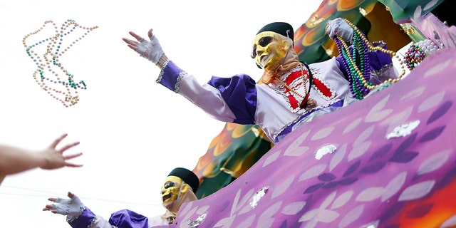 File - Mardi Gras beads are tossed at partygoers.