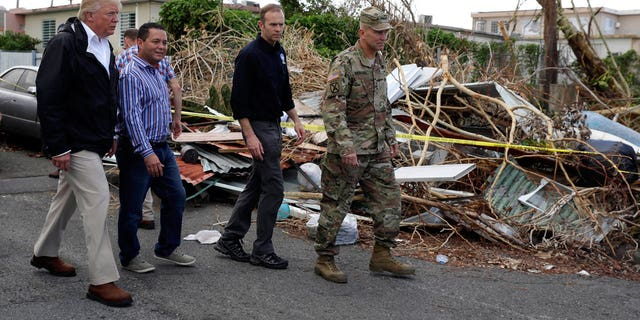 President Donald Trump walks with FEMA administrator Brock Long, second from right, and Lt. Gen. Jeff Buchanan, right as he tours an area affected by Hurricane Maria in Guaynabo, Puerto Rico, Tuesday, Oct. 3, 2017.