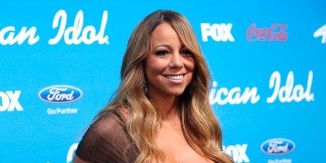 """Mariah Carey poses at the party for the finalists of the television show """"American Idol"""" in Los Angeles, California March 7, 2013."""