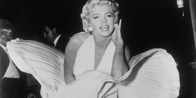 "In this Sept. 9, 1954 file photo, Marilyn Monroe poses over the updraft of a New York subway grate while filming ""The Seven Year Itch"" New York. The dress, created by Bill Travilla, is one of several items that will be up for auction in October 2018."