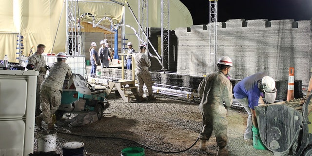 Marines from I Marine Expeditionary Force learn how to operate the world's largest concrete 3D printer as it constructs a 500-square-foot barracks hut at the U.S. Army Engineer Research and Development Center in Champaign, Illinois. (U.S. Marine Corps Courtesy Photo)