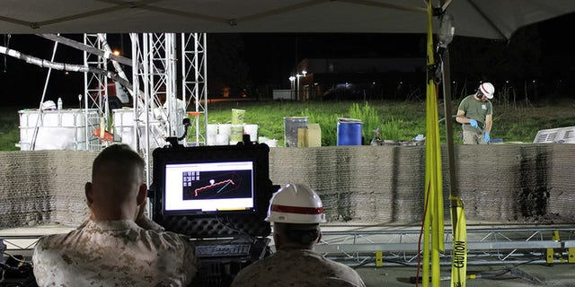 Marines from I Marine Expeditionary Force monitor the computer while the world's largest concrete 3D printer constructs a 500-square-foot barracks hut at the U.S. Army Engineer Research and Development Center in Champaign, Illinois. (U.S. Marine Corps Courtesy Photo)