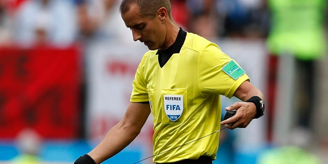 Referee Mark Geiger adjusts his ear piece used to communicate with his assistants during a group B match between Portugal and Morocco.