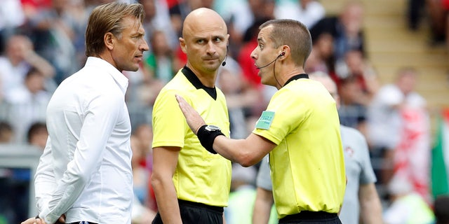 Referee Mark Geiger, right, talks to Morocco coach Herve Renard during a group B match between Portugal and Morocco.