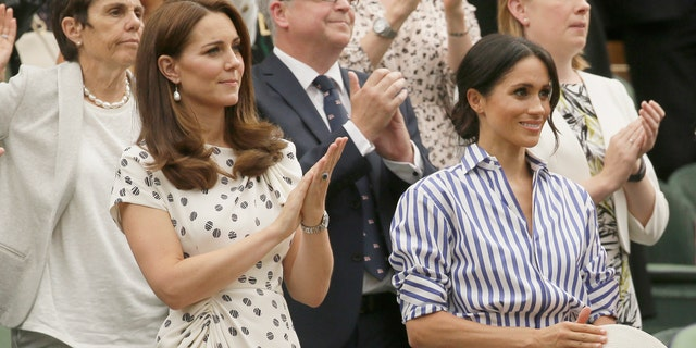 Duchess Kate Middleton and Meghan Markle watch the women's Wimbledon finale while Markle clings onto her straw hat she was unable to wear in the royal box on Saturday.