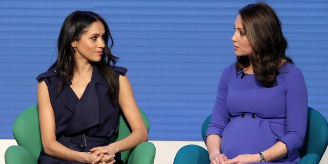 Meghan Markle and Kate share words during an event.
