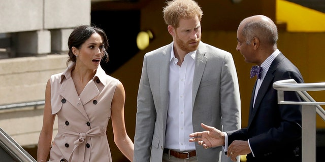 Britain's Prince Harry centre and his wife Meghan the Duchess of Sussex talk with the Lord-Lieutenant of Greater London, Sir Kenneth Olisa as they arrive for the launch of the Nelson Mandela Centenary Exhibition, marking the 100th anniversary of anti-apartheid leader's birth, at the Queen Elizabeth Hall in London, Tuesday, July 17, 2018. (AP Photo/Matt Dunham)
