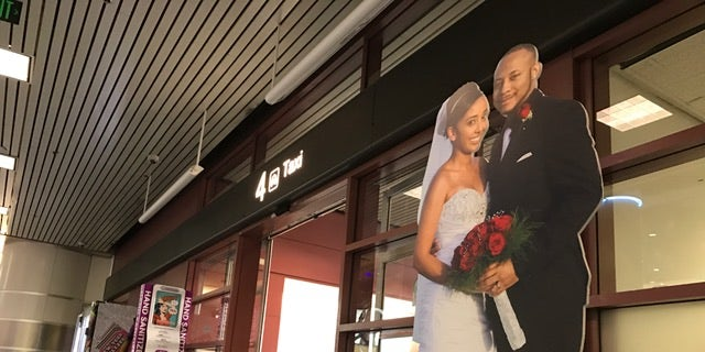 A cardboard cutout of a  couple beckons real couples to come apply for a marriage license. It is conveniently placed near the taxi stand at McCarran Airport in Las Vegas.