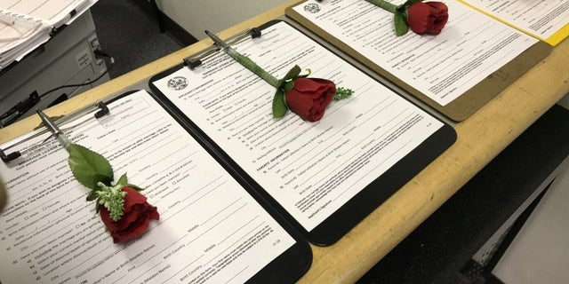 Roses are attached to marriage license applications waiting to be filled out. The licenses cost $77 at the pop-up marriage bureau kiosk at McCarran Airport in Las Vegas.