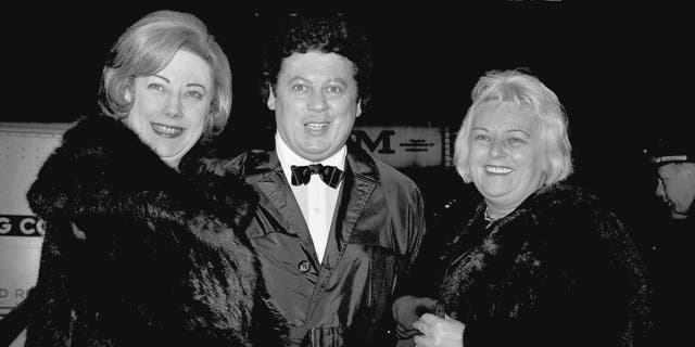 "FILE - In this March 16, 1965, file photo, comedian Marty Allen, center, arrives for the premiere of ""The Train"" with his wife Frenchie, right, and Rosemary Wilson, wife of columnist Earl Wilson, in New York. Allen's spokeswoman Candi Cazau says he died Monday, Feb. 12, 2018, of complications from pneumonia. His wife and performing partner Karon Kate Blackwell was by his side. He was 95. (AP Photo/John Lent, File)"