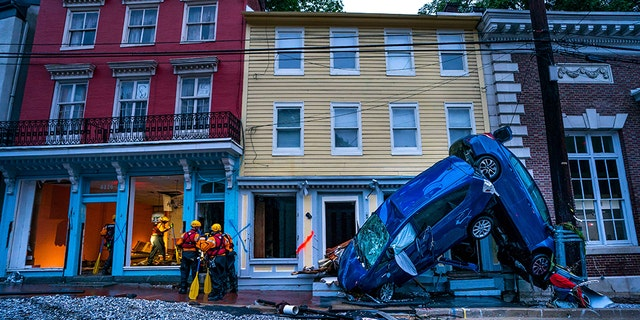 Rescue personnel examine damage on Main Street after a flash flood rushed through the historic town of Ellicott City.
