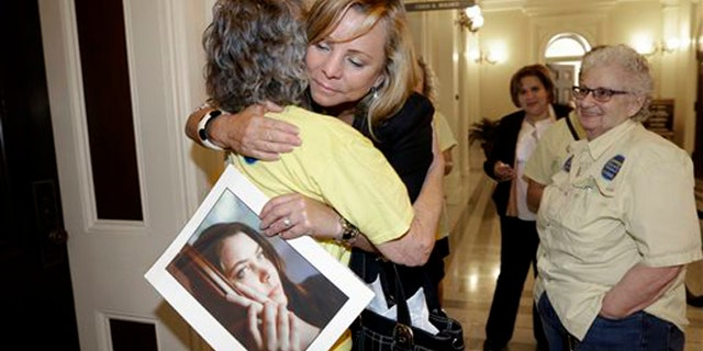 Sept. 9, 2015: Debbie Ziegler holds a photo of her daughter, Brittany Maynard, as she receives congratulations from Ellen Pontac, after a right-to die measure was approved by the state Assembly in Sacramento, Calif.