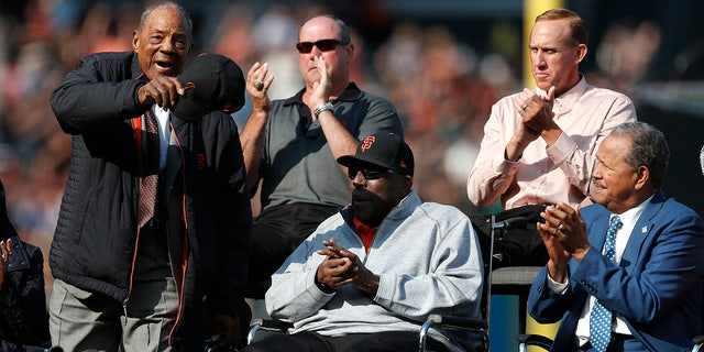 Former San Francisco Giants players Willie Mays, Will Clark, Kirk Rueter, Juan Marichal and Willie McCovey, clockwise from left, acknowledge fans during a ceremony to retire Barry Bonds' jersey number before a baseball game between the Giants and the Pittsburgh Pirates in San Francisco, Aug. 11, 2018.