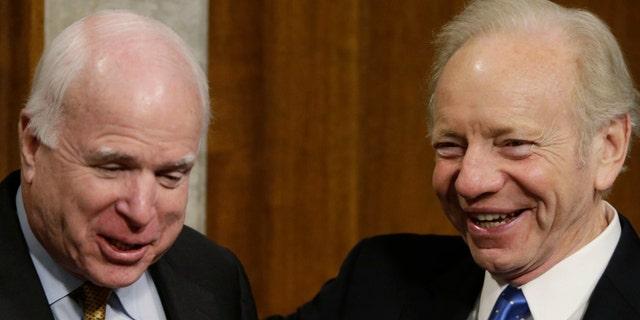 Sen. John McCain (R-AZ), left, jokes with Senator Angus King (I-ME) and former Senator Joe Lieberman (R) during a break in a confirmation hearing for Ashton Carter, U.S. President Barack Obama's nominee to be the secretary of defense, on Feb. 4, 2015.