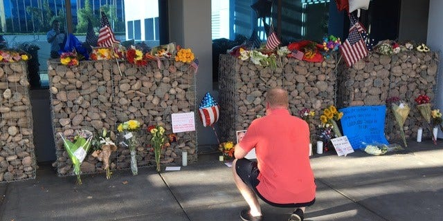 US Navy veteran pays his respects at memorial set up outside of Senator McCain's office