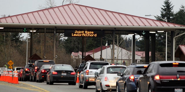 FILE: Commuters drive through the security checkpoint at the Madigan Army Hospital gate of Joint Base Lewis McChord (JBLM.)