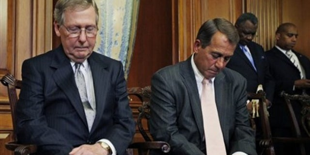 FILE: Senate Minority Leader Mitch McConnell, R-Ky., and House Republican Leader John Boehner, R-Ohio, bow their heads in prayer as they participate in a ceremony on June 16 to unveil plaques recognizing the contributions of enslaved African Americans in the construction of the United States Capitol.