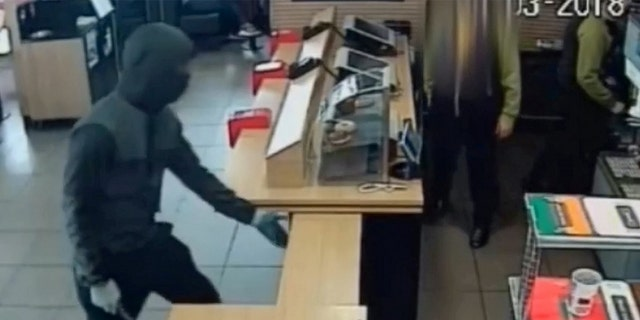The suspect lifts up the barricade that separates the employees from the dining area, grabs the box, and threatens a worker with the weapon before fleeing the store.