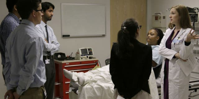 In this June 25, 2014 photo, Chief Medical Resident Julia Vermylen, right, critiques interns after a breaking bad news exercise during intern boot camp, taught by Northwestern Memorial Hospital and Northwestern University's Feinberg School of Medicine in Chicago. (AP Photo/Stacy Thacker)