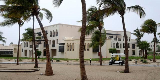 May 25, 2018: A club car passes the trees at a hotel in Salalah, Oman, as winds pick up.