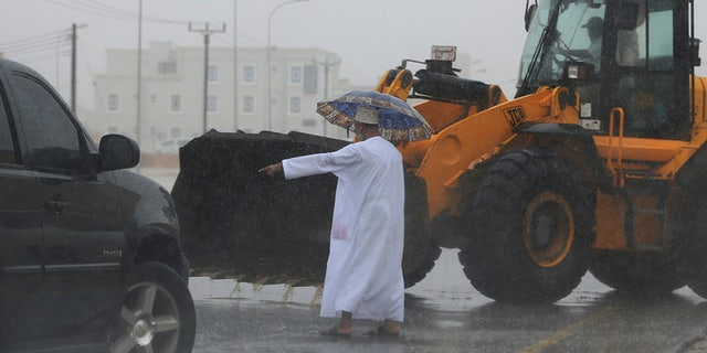 May 25, 2018: An Omani official gestures to a loader driver to tear away a road median to drain a flooded street in Salalah, Oman.