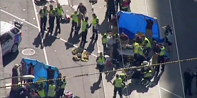 In this photo made from Australian Broadcasting Corp. video, medical workers offer aid to victims in Melbourne, Australia, Dec. 21, 2017.