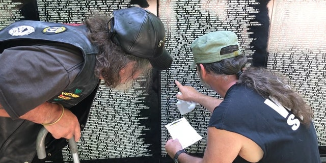 A Vietnam veteran receives help while searching for a fallen comrade's name on the Vietnam Traveling Memorial Wall.