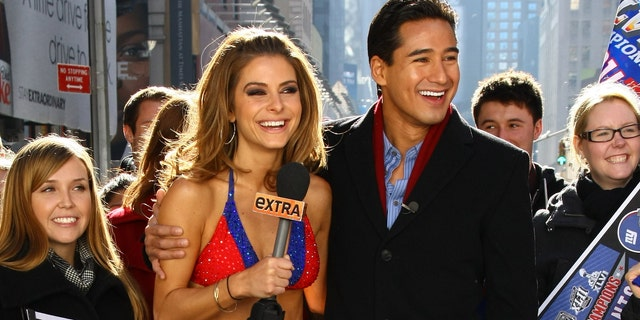 """NEW YORK, NY - FEBRUARY 06:  """"Extra"""" hosts Mario Lopez (R) and Maria Menounos, an avid New England Patriots fan, makes good on her Super Bowl bet with her fellow show correspondent, Giants fan AJ Calloway and bares all in a New York Giants Bikini in Times Square on February 6, 2012 in New York City.  (Photo by Neilson Barnard/Getty Images)"""