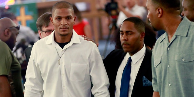 In this June 7, 2018, file photo, Robert Johnson, 35, left, leaves after his statement at New Beginnings Christian Church in Mesa, Ariz.