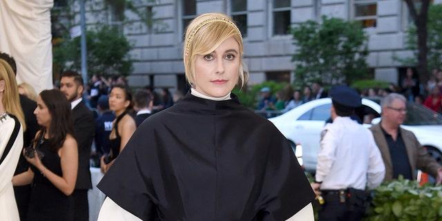 Director Greta Gerwig poses in a nun-like ball gown on the Met Gala carpet.