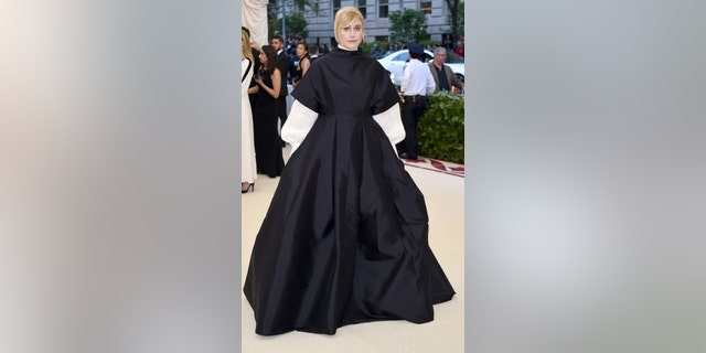 Director Greta Gerwig poses in a nun-like ball gown on the Met Gala carpet.