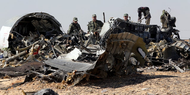 Military investigators from Russia stand near the debris of a Russian airliner at the site of its crash last November.