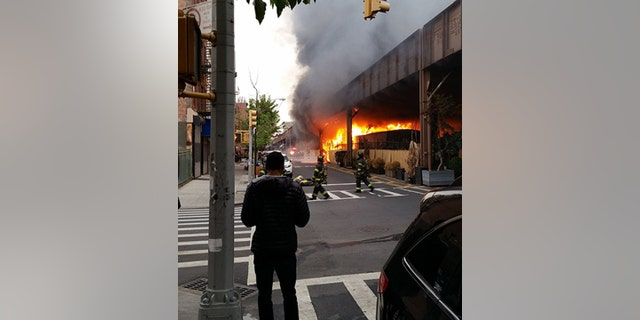 May 17, 2016: Firefighters battle a fire under the Metro-North railroad tracks in New York.