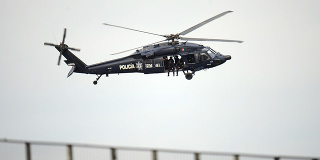 GUADALAJARA, MEXICO - OCTOBER 14:  A federal police helicopter flies over before the Opening Ceremony for the XVI Pan American Games at Omnilife Stadium on October 14, 2011 in Guadalajara, Mexico.  (Photo by Dennis Grombkowski/Getty Images)