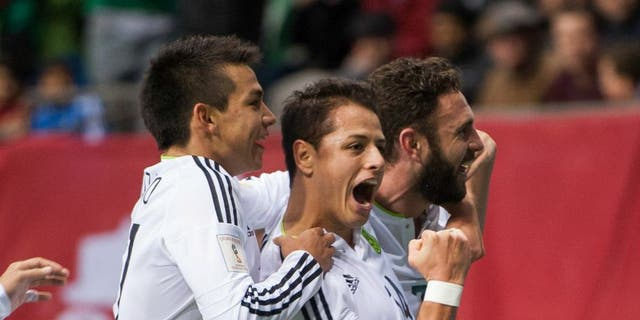 """VANCOUVER, BC - MARCH 25: Javier """"Chicharito"""" Herhandez #14 of Mexico is congratulated by teammates Javier Aquino #11 and Miguel Layun #7 of Mexico after scoring a goal against Canda during FIFA 2018 World Cup Qualifier soccer action at BC Place on March 25, 2016 in Vancouver, Canada. (Photo by Rich Lam/Getty Images)"""