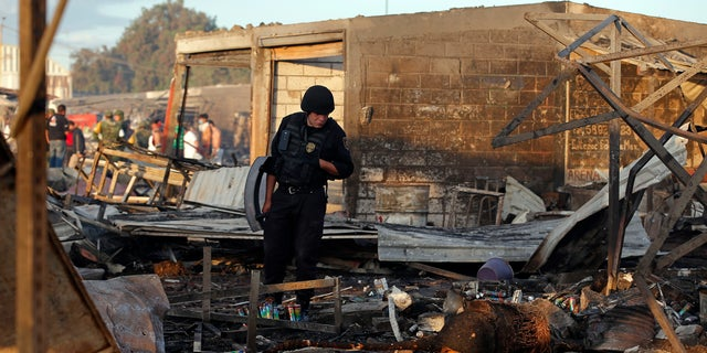A Mexico State policeman looks through the scorched ground of the open-air San Pablito fireworks market, in Tultepec, outskirts of Mexico City, Mexico, Tuesday, Dec. 20, 2016.