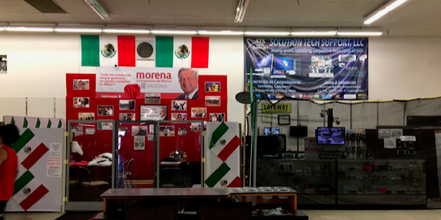 In Phoenix, there is a make-shift booth set up in a Latino central market that functions as an information booth for Mexican voters wanting to mail-in their ballots.
