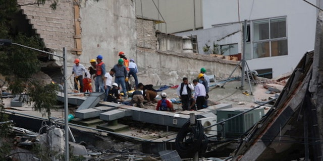 People clear rubble after an earthquake hit Mexico City, Mexico September 19, 2017.