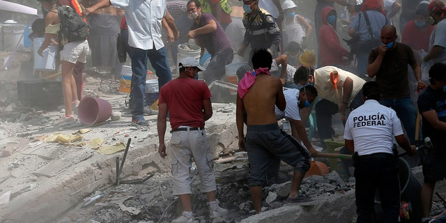 Volunteers search a building that collapsed after an earthquake, in the Roma neighborhood of Mexico City, Sept. 19, 2017