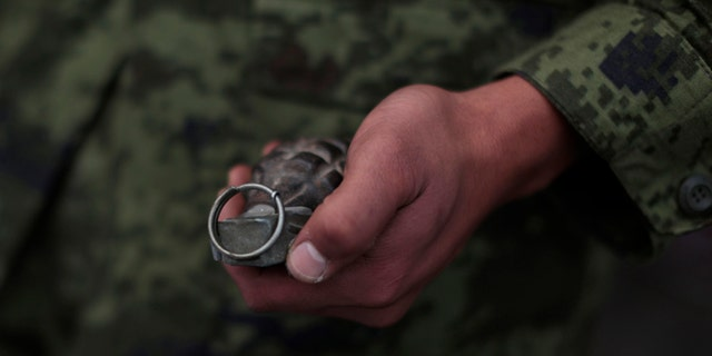 In this file photo, a soldier holds a grenade in Mexico City, Mexico.
