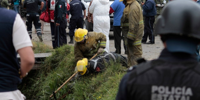 March 15, 2013: Emergency workers search for human remains in a ditch after a truck loaded with fireworks exploded during a religious procession in the town of Nativitas, Mexico.